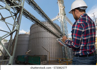 Engineering working hold tablet in front of set of storage tanks raw material agricultural crops feed mills. industry background