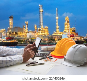 engineering working on computer tablet  against beautiful oil refinery background