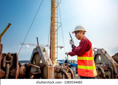 engineering working with winch machinery takes control job command safety by communication walkie talkie to concerning party at high skill and level of stage working