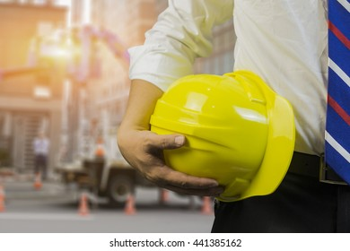 engineering,engineer or worker hold in hand yellow helmet ,discussing blueprint next to electrical substation for workers security in front of construction blur background.vintage tone