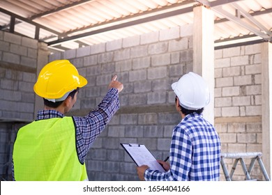 Engineers or architects with customers or contractors are discussing the details of fixing the structure of the house roof. Inspect and consult for quality work.