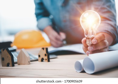 Engineers or architects holding Lightbulb and note on blueprint in working site.idea Construction and structure concept.