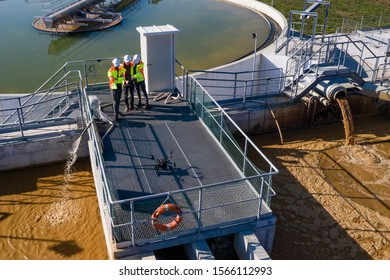 Engineers assesing waste water treatment plant with industrial drone