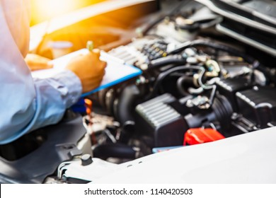 Engineers are checking cars. The light is golden at sunset.