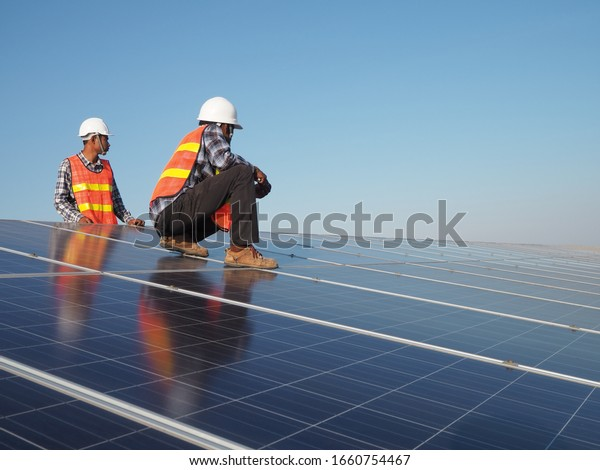 Engineers are checking solar cells in the summer.