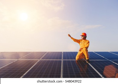 Engineers checking solar panels,Holding the bulb on the Solar Panel. Solar Energy ,The concepts of Clean Energy.