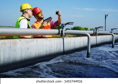 Engineers controlling a quality of water ,aerated activated sludge tank at a waste water treatment plant