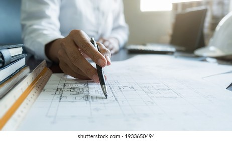 Engineers discuss a blueprint while checking information on a tablet computer in a office.