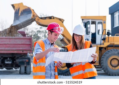 Engineers examining plans on construction site