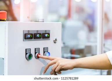 Engineer's hand push red button to shutdown temperature control machine. Temperature control panel cabinet contain digital screen display for temperature gauge. Heat control in industrial factory.