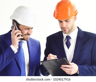 Engineers with happy faces. Architecture, engineering, success concept. Business partners look at building plan. Architects discuss project. Entrepreneur and architect with plans and smartphone.