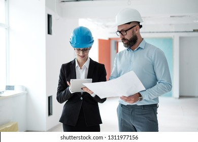 Engineers in hardhats have conversation