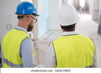 Engineers in hardhats having conversation