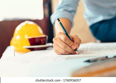 engineers holding a pen pointing to a building and  drawing outlay construction plan as guide for builders with details. Engineer design and writing blueprint.