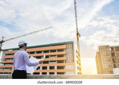Engineers looking blueprint  Building is under construction