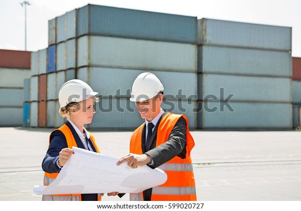 Engineers looking at blueprint in shipping yard