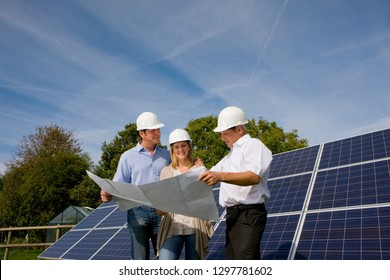 Engineers looking at plans standing next to large solar panels