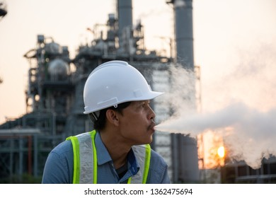 Engineers male smoking e-cigarette in front of power plant. Energy power station area. Relax from work concept