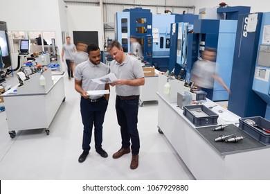 Engineers Meeting On Factory Floor Of Busy Engineering Workshop