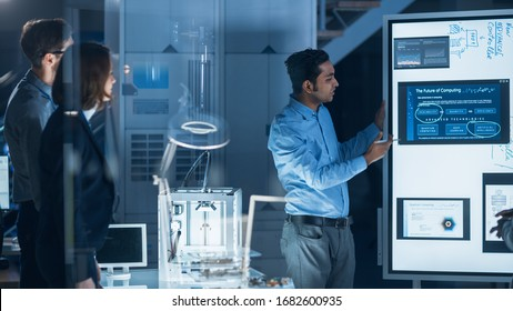 Engineers Meeting in Technology Research Laboratory: Male Engineer Leads Presentation Using Digital Whiteboard, Shows Machine Blueprint, Data Analytics and Neural Network while Colleagues Listening