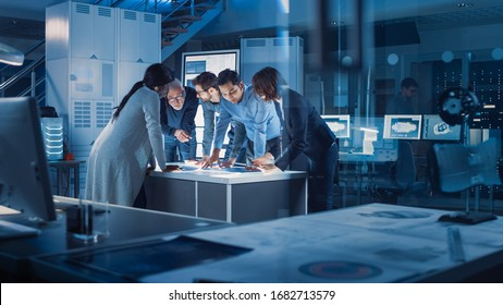 Engineers Meeting in Technology Research Laboratory: Engineers, Scientists and Developers Gathered Around Illuminated Conference Table, Talking and Finding Solution Inspecting Industrial Engine Design