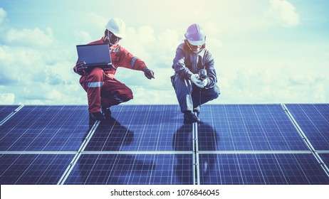 engineers operating and check generating power of solar power plant on solar rooftop; technical team in different industry uniform on level of job description