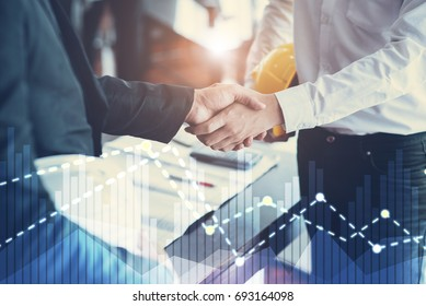 Engineers shaking hands agreement partners to work in conference Business negotiations with graphic diagram statistics