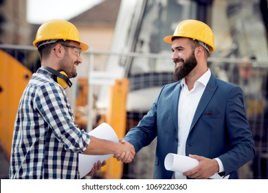 Engineers shaking hands at construction site.