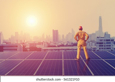 Engineers, standing on the roof, solar panels and look at the city need power. Green energy for the city (concept).