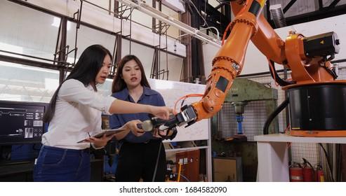 Ingenieure Team Control Robotic Arm arbeitet und bewegt. Sie sind in einem High Tech Forschungslabor mit moderner Ausrüstung. Technologie- und Innovationskonzept.