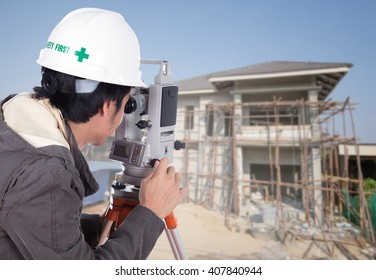 Engineers use tacheometer or theodolite with house construction site background
