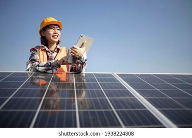 Engineers using laptop to install solar panels on an organic farm. Solar panel technician