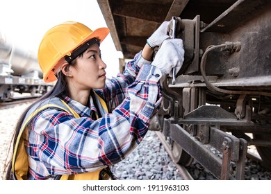 Engineers woman working on train garage site and using wrench for repair traction motor of train. Service and Technician concept.