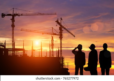Engineers work in front of the construction site at sunset.