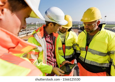 Engineers and workers assesing wastewater plant performance on tablet