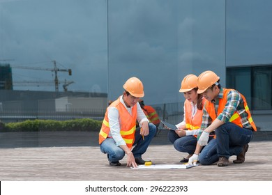 Engineers working with blueprint at the construction site