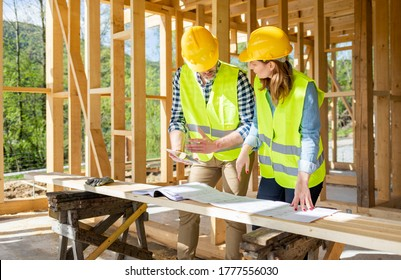 Engineers working on construction site holding blueprints of wood frame house