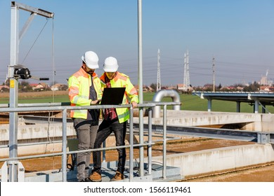 Engineers working on water treatment plant with laptop and measuring sensors
