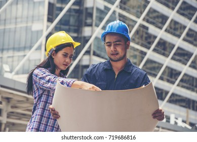 Engineerwoman and worker with helmet developer holding blueprint  working Confident  outdoors in construction site
