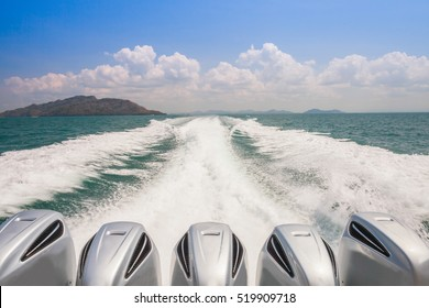 Engines of speed boat are driving along waving of water on ocean with mountain and cloudy sky located south of Thailand