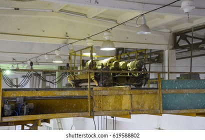 Engines that control the operation of the hoist. Lift motors on a steel frame under the ceiling.
