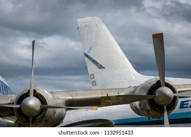 Engines and wing of a decommissioned prop passenger airplane with another airplane in the background and dark cloudy sky