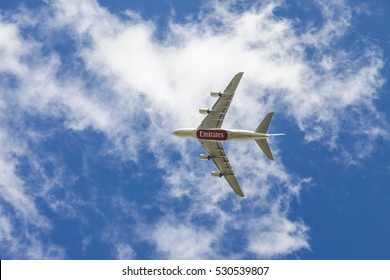 England. August 28 2014 : Underside view of a Boeing 777 jet aeroplane with Emirates  logo. Plane in flight with blue sky background.