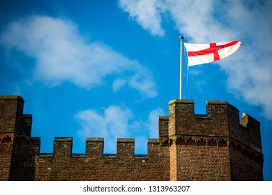 England flag flying above castle fortifications with blue sky