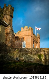 England flag flying over castle walls on sunny day