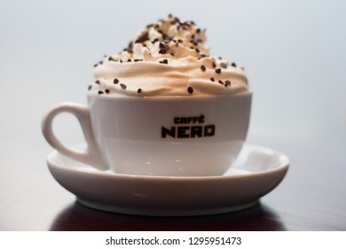 ENGLAND, IPSWICH - April 22, 2012: Hot drink from Caffe Nero in a white branded cup on a saucer with white background.  On top of the drink is whipped cream and chocolate sprinkles.