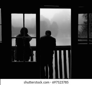ENGLAND, NOVEMBER 2015: A couple standing at the balcony overlooking a lake at Winkworth Arboretum