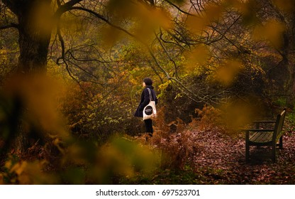 ENGLAND, NOVEMBER 2015: A lone girl ruminates among trees with brown leaves at Winkworth Arboretum