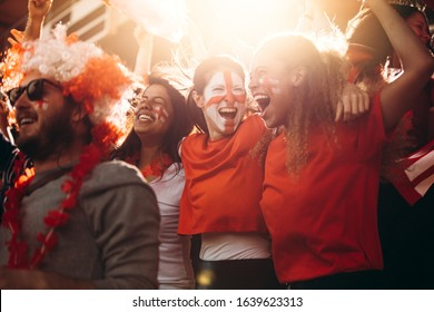 England soccer supporters cheering in stands. Women with England flag painted on their faces having fun in fan zone at stadium.