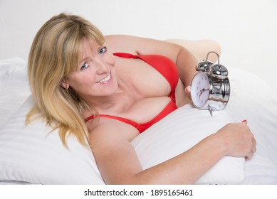 England, UK. 2014. Attractive woman in red underwear laying on a bed with an alarm clock.
